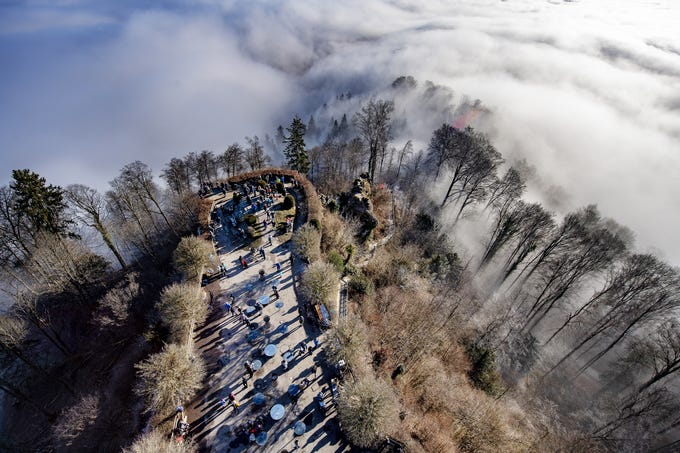 People stand on an overlook above the fog line on the Uetliberg in Zurich, Switzerland on Jan. 2, 2020.
