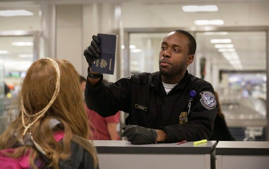 U.S. Customs and Border Protection officers screen international passengers arriving at the Dulles International Airport in Virginia, November 29, 2016.
