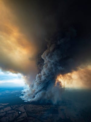 Smoke rises from wildfires burning in East Gippsland, Victoria. Thousands of tourists fled Australia's wildfire-ravaged eastern coast ahead of worsening conditions as the military started to evacuate people trapped on the shore further south. Cooler weather has aided firefighting and allowed people to replenish supplies.