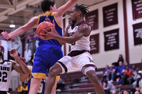 McMurry's Dedrick Berry (3) makes a pass in the air along the baseline against LeTourneau.