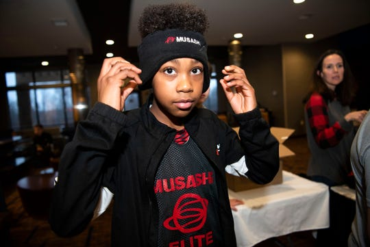 Keyvon Fitzpatrick tries on his new Musashi Elite basketball league uniform on Friday, Jan. 3, 2019 at Courtyard by Marriott in Battle Creek, Mich.