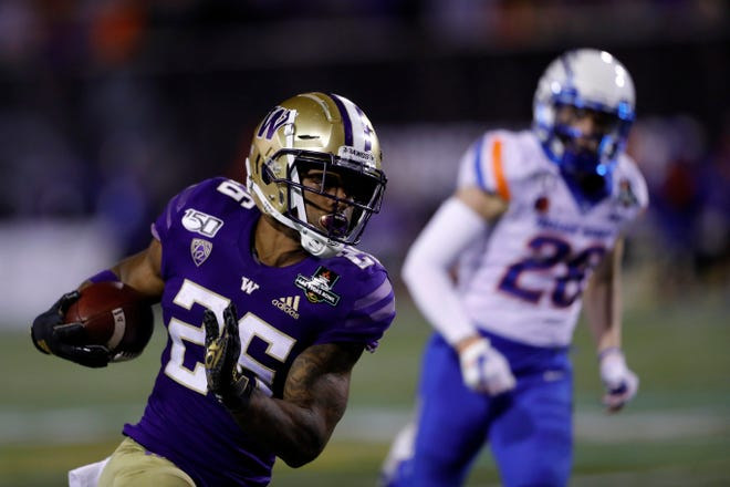 Washington running back Salvon Ahmed (26) carries the ball past Boise State defensive back Kekaula Kaniho (28) during the second half of the Las Vegas Bowl NCAA college football game at Sam Boyd Stadium, Saturday, Dec. 21, 2019, in Las Vegas.