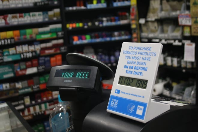 A sign indicating the legal age to buy tobacco and vaping products at the register of Smoke Train in East Bremerton. Washington state's law raising the age to buy such products went into effect Jan. 1.