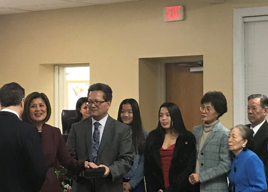 Cherry Hill Mayor Susan Shin Angulo stands with family members as she is sworn in Thursday night by Rep. Donald Norcross, right.