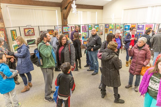 Children examine the works of other young artists at the Children's Environmental Art Show at the Environmental Education Center from Tuesday, Jan.7, to Sunday, Feb.2.