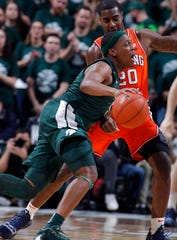 Michigan State's Cassius Winston, front, drives against Illinois' Da'Monte Williams (20) during the first half of an NCAA college basketball game Thursday, Jan. 2, 2020, in East Lansing, Mich. (AP Photo/Al Goldis)