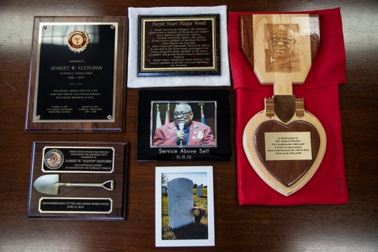 Photos of Army Pfc. Robert Fletcher, his headstone in Arlington National Cemetery and plaques are photographed at First Presbyterian Church of Ann Arbor, Thursday, Jan. 2, 2020.