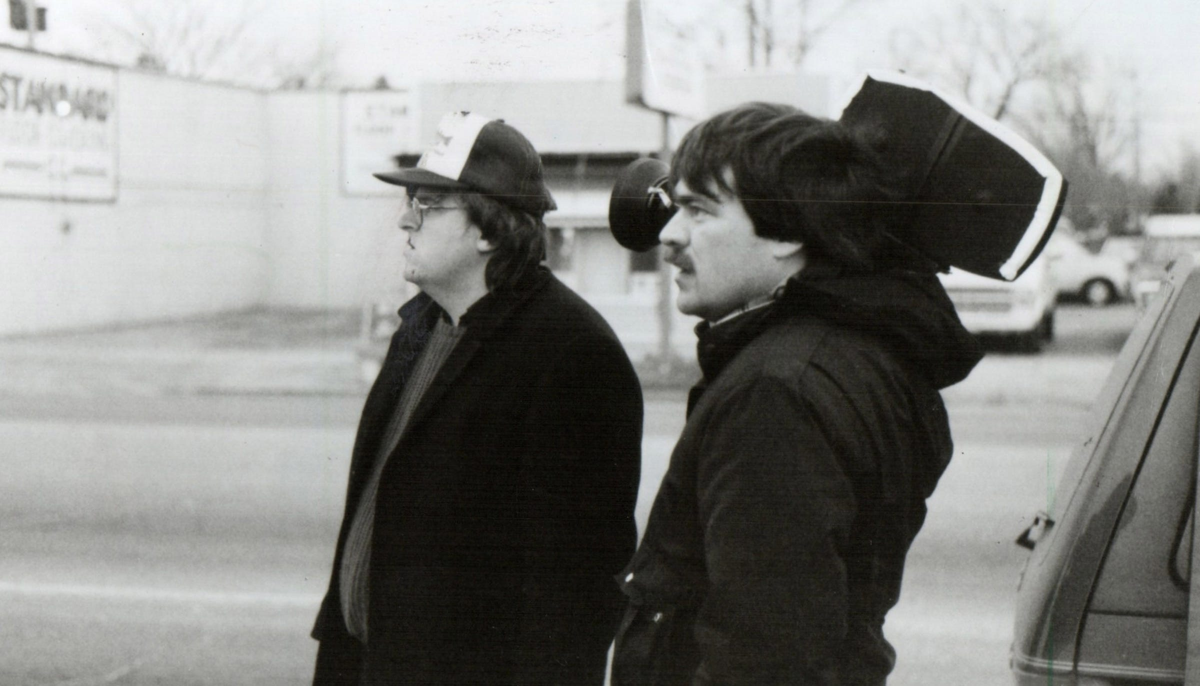 """Michael Moore (left), director of the feature length documentary, """"Roger & Me"""" and camera John Prusak (right) prepare to shoot."""