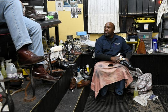 Red Jazz Shoe Shine owner David Boggon talks with Dwayne Richardson, left, in the shoe shine shop on E. Euclid and Oakland in Detroit.  A part of Euclid is being developed into a mix of art incubator, communally-owned housing and business development.