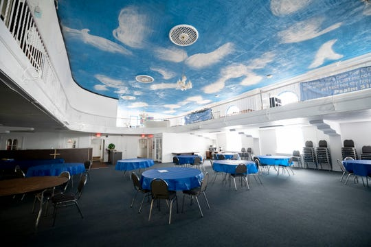 The banquet hall inside the Pure Word Missionary Baptist Church in Detroit features a blue sky full of dove-like clouds.