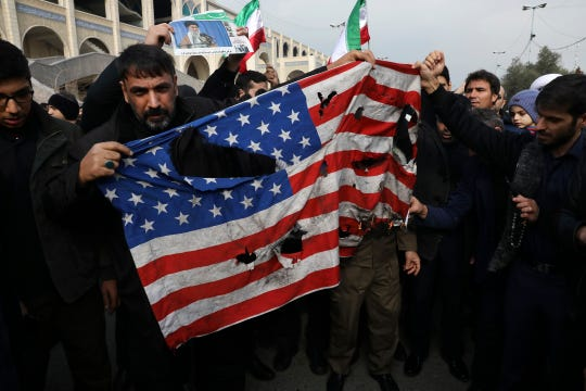 Protesters burn a U.S. flag during a demonstration over the U.S. airstrike in Iraq that killed Iranian Revolutionary Guard Gen. Qassem Soleimani, in Tehran, Iran, Jan. 3, 2020.