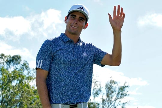 Joaquin Niemann waves after making birdie on the 18th green.