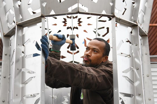 Artist Joseph Hurd works on the stainless steel Arabesque-style canopy with islamic patterns built as a communal meeting space in Detroit.