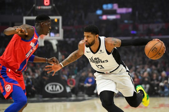 Los Angeles Clippers forward Paul George, right, tries to drive past Detroit Pistons guard Tony Snell.