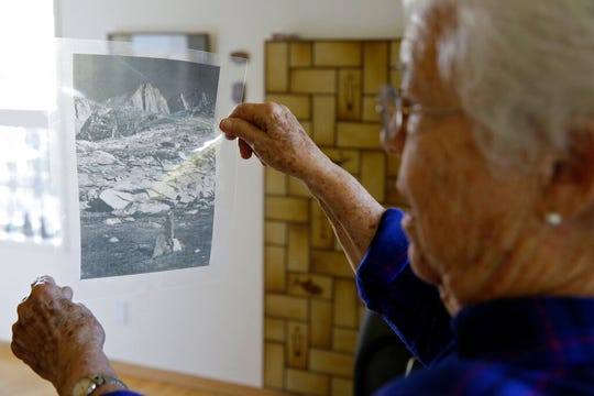 In this photo taken Tuesday, Oct. 22, 2019, Joan Busby looks at a transparency of where her mother found human remains in 1945 of Giichi Matsumura on Mount Williamson, at her home in Mill Valley, Calif. A burial party from Manzanar internment camp ascended the mountain, located the body, buried it and left a small pile of granite slabs to mark the grave.