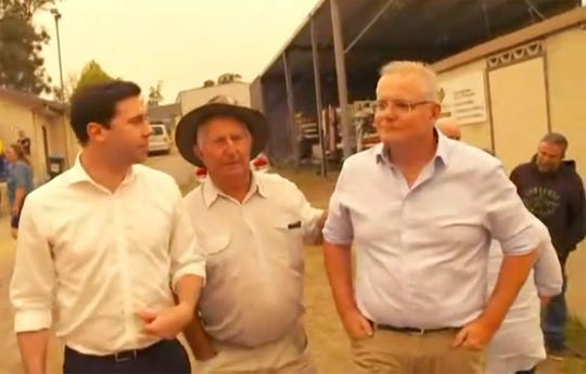 This still image taken from video provided by AuBC, Australian Prime Minister Scott Morrison is confronted by angry residents as he visited a wildfire-ravaged Cobargo, in New South Wales on Thursday, Jan. 2, 2020.
