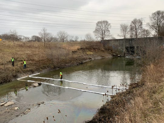 Workers with the Macomb County Public Works Office place containment booms at the confluence of the Schoenherr Relief Drain and the Red Run, near 14 Mile and Schoenherr roads, to contain a petroleum spill Jan. 3, 2020.