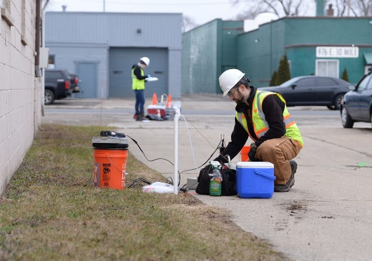 Marc Messina of Mannik Smith Group, collects water samples outside the facility where green ooze was recently detected seeping out and onto the shoulder of I-696 in Madison Heights, Michigan.