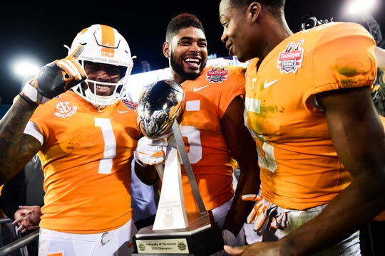 Tennessee wide receiver Jauan Jennings (15) holds the trophy next to wide receivers Marquez Callaway (1) and Josh Palmer (5) after the team's 23-22 win over Indiana in the Gator Bowl.