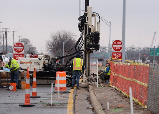 Contractors from Tetra Tech Engineering services company use a drill to get soil samples to detect contamination near the facility where the green ooze was seeping out and onto the shoulder of I-696 in Madison Heights, Michigan.