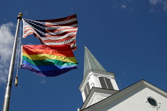 FILE - In this April 19, 2019, file photo, a gay pride rainbow flag flies along with the U.S. flag in front of the Asbury United Methodist Church in Prairie Village, Kan.