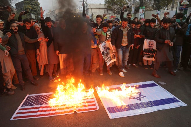 Pakistani Shiite Muslims burn representations of US and Israeli flags during demonstration over the U.S. airstrike in Iraq that killed Iranian Revolutionary Guard Gen. Qassem Soleimani, near the U.S. Consulate in Lahore, Pakistan, Friday, Jan. 3, 2020.