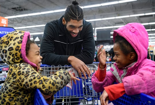 University of Evansville's K.J. Riley, center, waits in line to check out with 7-year-old twins Ka'Laya and Ka'Liza Barnes during the Christmas Wish event held at Academy Sports + Outdoors in Evansville, Ind., Wednesday evening, Dec. 18, 2019. UE Basketball Coach Walter McCarty and Academy Sports teamed up to give 18 local children $150 to shop for themselves while spending time with the team.