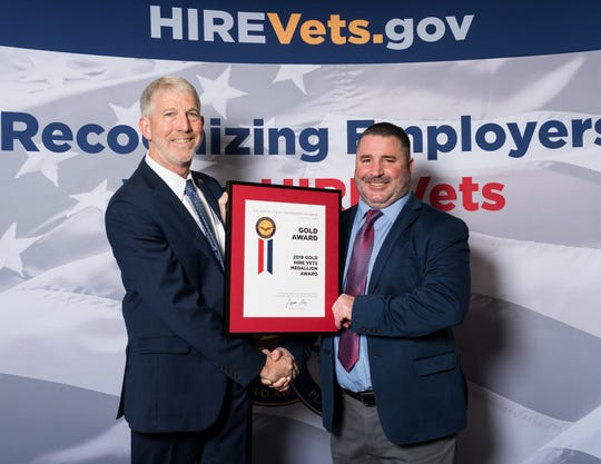 Peer Technical Vice President of Veterans Affairs and Finance Bruce Welnetz, right, shakes hands with Department of Labor Department of Labor Veterans Employment Deputy Assistant Secretary of Management and Policy Sam Shellenberger  at ceremony on Nov. 6 in Washington, D.C.