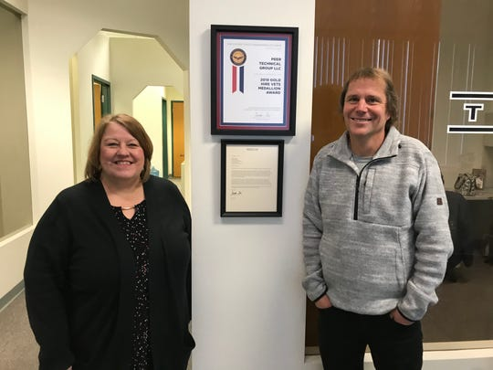 Peer Technical Managing Partner Betty Fritch and Owner Michael Clausen stand beside the 2019 Gold HIRE Vets Medallion Award and letter received from the United States Department of Labor on Thursday, Jan. 2, 2020 at their 74 S. Main St. office.