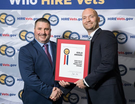 Peer Technical Vice President of Veterans Affairs and Finance Bruce Welnetz, left, shakes hands with Department of Labor Veterans' Employment Training Service Chief of Staff Jonathan VanderPlas at ceremony on Nov. 6 in Washington, D.C.