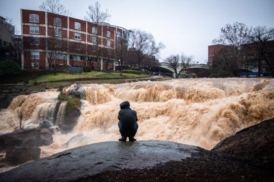Bryant Attaway, of Easley, watches the falls at Falls Park during a period of heavy rain Friday, January 3, 2020.