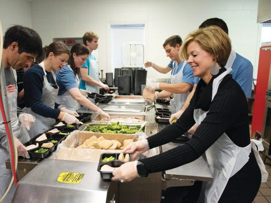 Employees of Elliot Davis volunteer at the Meal on Wheels of Greenville by helping prepare packaged meals.