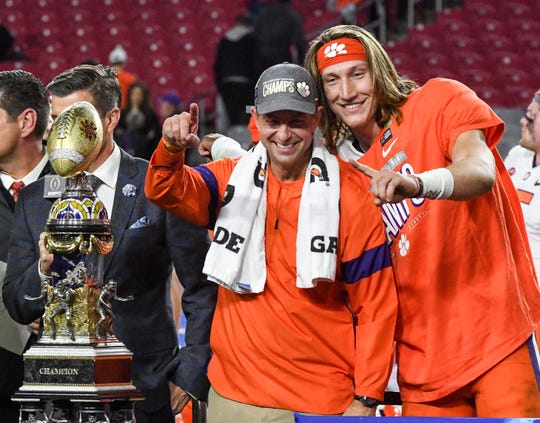 Clemson Head Coach Dabo Swinney and Clemson quarterback Trevor Lawrence (16) celebrate a 29-23 win over Ohio State at the PlayStation Fiesta Bowl at State Farm Stadium in Glendale, Arizona Saturday, December 28, 2019.