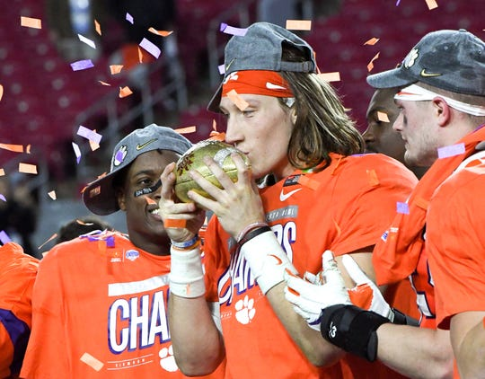 Clemson quarterback Trevor Lawrence (16) celebrates with teammates and the trophy a 29-23 win over Ohio State at the PlayStation Fiesta Bowl at State Farm Stadium in Glendale, Arizona Saturday, December 28, 2019.