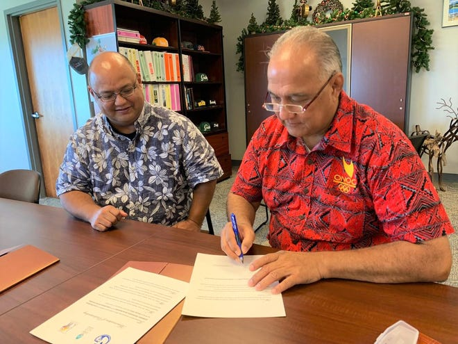 Guam Department of Education Superintendent Jon Fernandez, left, signs a memorandum of understanding with Ricardo Blas, president of the Guam National Olympic Committee on Jan. 3. The agreement is for the GNOC to offer athletes awareness training, as well as certification for its coaches.
