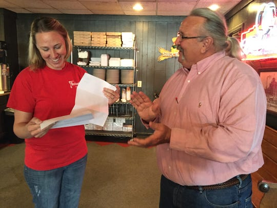 John Stroud presents downtown restaurant owner Christi Osborne with approval for sidewalk dining in 2016.