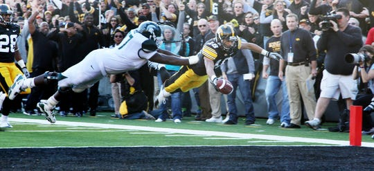 Micah Hyde dives for the North end at Kinnick Stadium to complete a dramatic pick-six runback that gave Iowa a 17-0 first-quarter lead against the fifth-ranked Spartans.