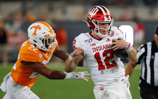 Jan 2, 2020; Jacksonville, Florida, USA; Indiana Hoosiers quarterback Peyton Ramsey (12) is chased out of bounds by Tennessee Volunteers defensive back Jaylen McCollough (22) during the second quarter in the 2020 Taxslayer Gator Bowl at TIAA Bank Field.