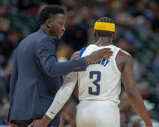 Victor Oladipo chats with teammate Aaron Holiday, late in their loss to the Denver Nuggets at Indiana Pacers, Bankers Life Fieldhouse, Indianapolis, Thursday, Jan. 2, 2020. Indiana lost 124-116.