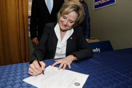 U.S. Sen. Cindy Hyde-Smith, R-Miss., puts her signature to a qualifying statement of intent as a candidate for the Republican nomination for United States Senator, Friday, Jan. 3, 2020, at the state GOP headquarters in Jackson, Miss. Hyde-Smith filed papers to run at party headquarters, with many Republican statewide elected officials in attendance and is expected to campaign by emphasizing her loyalty to President Donald Trump. (AP Photo/Rogelio V. Solis)