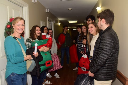 The Karns High School DECA club members line the hallway contemplating which Christmas song they should sing at Autumn Care Assisted Living Friday Dec. 20.