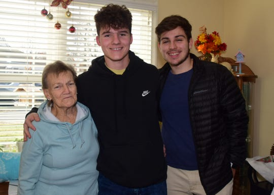 Patricia Warren gets a visit from Karns High School DECA members Sam Pinkston, 16, and Alen Nukic, 18,  at Autumn Care Assisted Living Friday Dec. 20.
