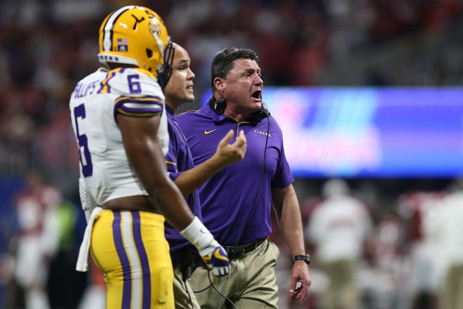 Dec 28, 2019; Atlanta, Georgia, USA; LSU Tigers head coach Ed Orgeron (right) and defensive coordinator/linebackers coach/associate head coach Dave Aranda (middle)  signal to the Tigers defense during the third quarter of the 2019 Peach Bowl college football playoff semifinal game against the Oklahoma Sooners at Mercedes-Benz Stadium. Mandatory Credit: Brett Davis-USA TODAY Sports