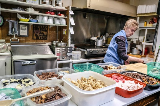 Mary Dershem, co-owner of Dershey's Cafe in St. Johns, helps out in the kitchen when needed. The cookies and sweets are for customers to try on their way out Friday, Jan. 3, 2020.