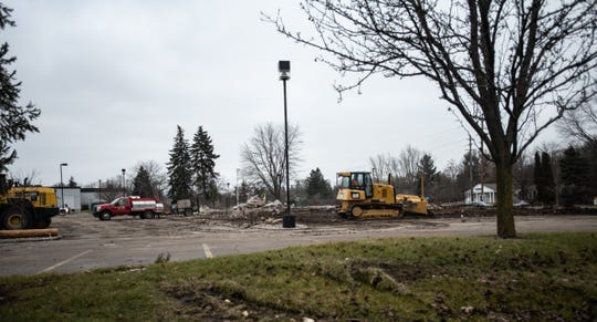 Workers raze a former restaurant site near the southeast corner of E. Grand River Avenue and Okemos Road , Friday, Jan. 3, 2019, where a new shopping center will be built.