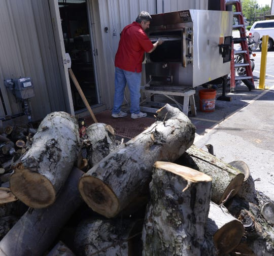 Stacks of fruitwood in the foreground as  Regan Louchart tends the smoker at the newly opened Capital City BBQ in a 2015 file photo.