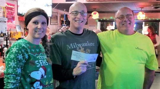 Janine Facer and Lonz from Lonz's Tannery Club present a check for $600 to Dave Jirikowic from the Miracle Splash. The money is used for underprivileged children in Manitowoc County.