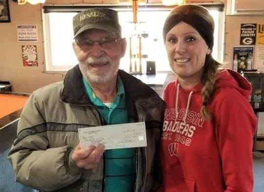 Janine Facer from Lonz's Tannery Club presenting a check for $600 to Jack Woodkey from Two Rivers Ecumenical Pantry. Money was raised from an Ugly Sweater Party in December.