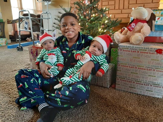 Roman Malcom, age 8, is shown with his sister, Bliss, left, and brother, Jabez, right, prior to opening Christmas gifts. Roman and his mother, Shannel Malcom, were involved in a serious car crash in November that left his mother with multiple injuries. Shannel Malcom said folks in Marion County have rallied around her family since the crash to provide help.