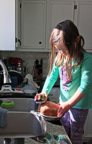 Mara Sherwood scrubs a sweet potato. Getting kids involved in meal prep can make them more willing to try new foods.